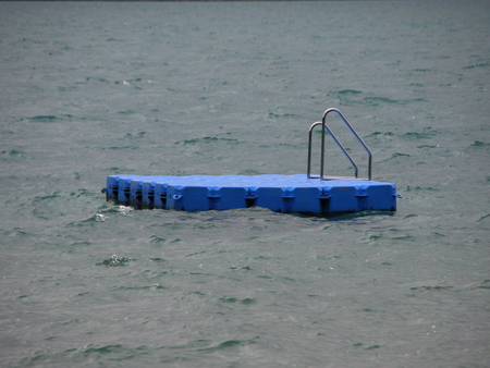Isolated Blue Ponton Swimming Platform on Stormy Cold Water