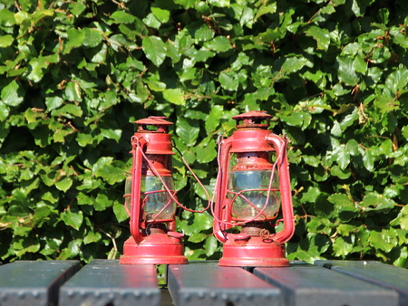 laterns: Two Red Rusty Lanterns on Black Table Outside
