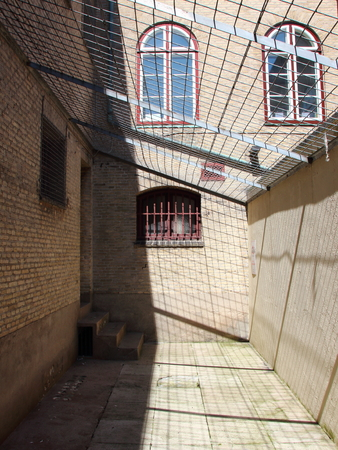 Inside of Jail Yard with Metal Grid Roof and Red Bars