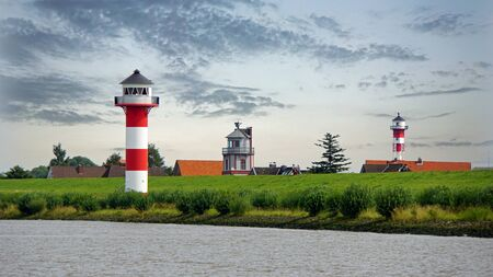 seawall: lighthouse on seawall at german river elbe near hamburg Stock Photo