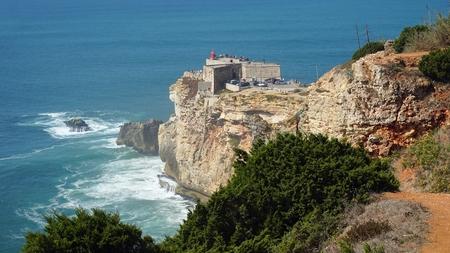 small lighthouse near portuguese city of nazare Standard-Bild - 114258407
