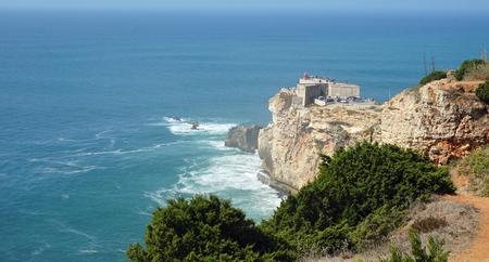 small lighthouse near portuguese city of nazare Standard-Bild - 114258385
