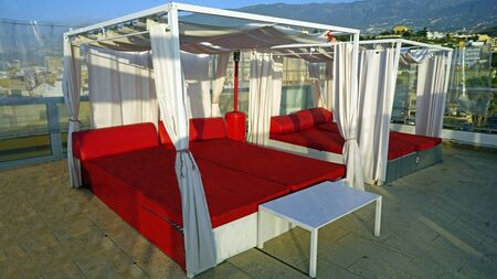 luxury red sunbed on a rooftop bar in spain Stockfoto