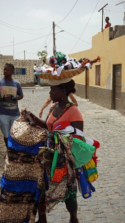 santa maria, cape verde, circa june 2018: traditional dressed african lady selling local products
