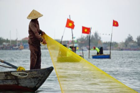vietnamese fisherman on small boat fishing with fishnet Imagens - 143138097