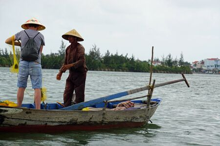 european tourist gets teached in traditional vietnamese net fishing Imagens - 143138336