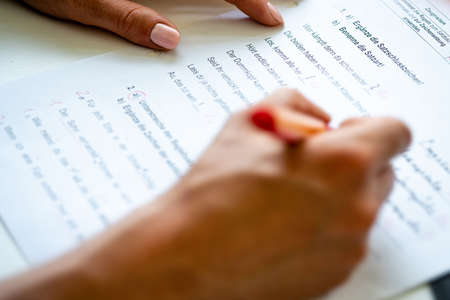A woman is correcting a test in german language. Фото со стока