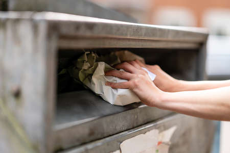 Woman putting paper in a container for recycling in Germany. Фото со стока