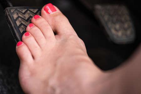 Een meisje rijdt op blote voeten in haar auto.