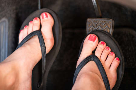 A girl is driving her car wearing flip flops. Stockfoto