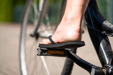 A girl is riding her bike with flip flops. Standard-Bild