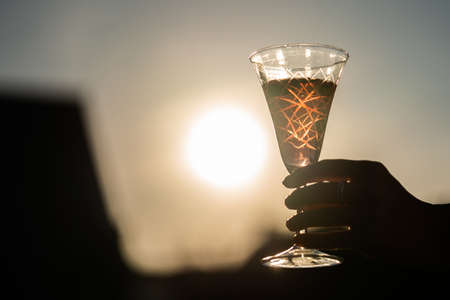 A glass of wine is being held by a woman right at the sunset.