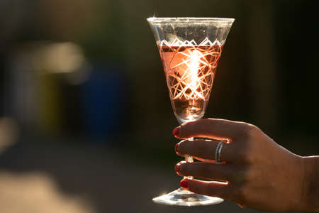 A glass of wine is being held by a young woman with the sun backlighting. Standard-Bild