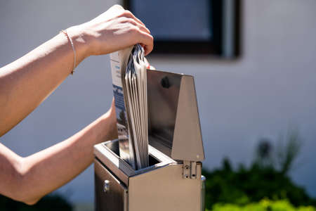 A woman takes a newspaper off a mailbox. 版權商用圖片