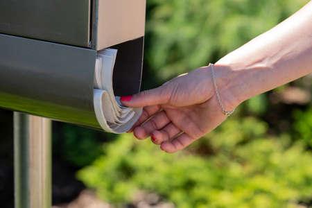A Woman takes the newspaper off a mailbox. Фото со стока