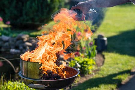 Las llamas en una parrilla de carbón se encienden con un encendedor líquido para parrilla.