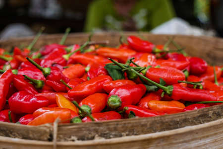 A wooden bowl filled with red chilis. Standard-Bild