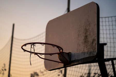 A basketball basket on a streetball field during dawn. Standard-Bild