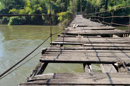 zeer oude opknoping voetgangersbrug over de rivier Stockfoto