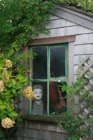 lattice window: Spooky cottage window in Nantucket.  Stock Photo