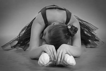 ballerina shoes: Black and white foto of young stretching ballerina