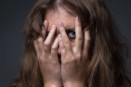 Frightened girl in water droplets on grey background Reklamní fotografie
