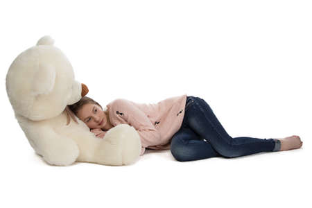 blessedness: Photo of teenage girl lying with teddy bear on white background