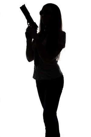 Silhouette of spy woman with gun on white background photo