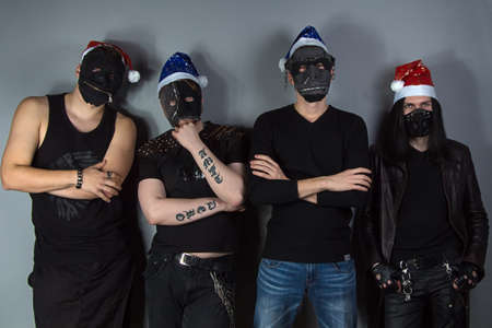 Photo of the man metal band in christmas hats on gray background photo