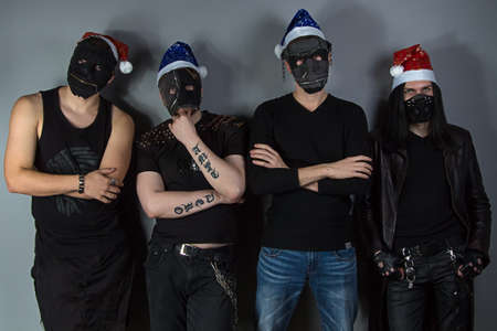 Image of the mans metal band in christmas hats on gray background photo
