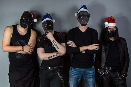 Portrait of the mans metal band in christmas hats on gray background photo