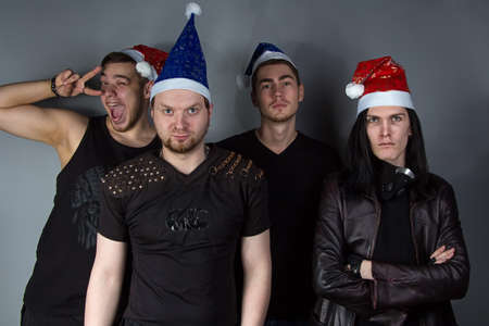 Portrait of the mans metal band in red and blue christmas hats on gray background photo