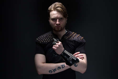 Photo of the young man with arms crossed on black background photo