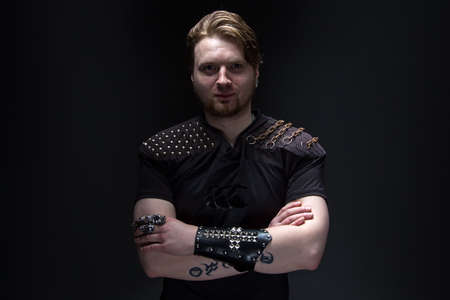 Portrait of the young man with arms crossed on black background photo
