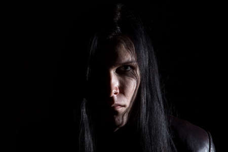 Photo of the brunet man with long hair on black background Stock Photo