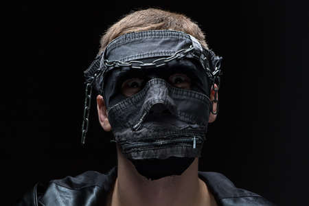 madman: Image of madman in handmade mask on black background