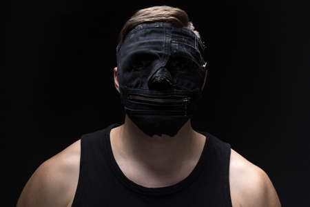 Photo of the young man in handmade mask on black background Stock Photo