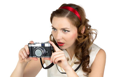 Portrait of the photographing woman with retro camera on white background