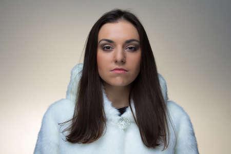 manteau de fourrure: L'image de la jeune femme en manteau de fourrure sur fond clair