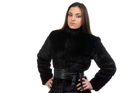 fur coat: Photo of the serious brunette in fur coat on white background