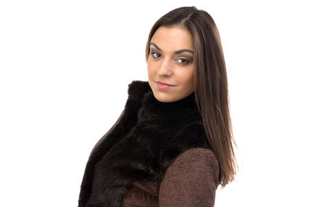 Portrait of attractive woman in brown fur waistcoat on white background photo