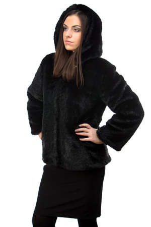 Portrait of woman in black fur coat with hood on white background photo