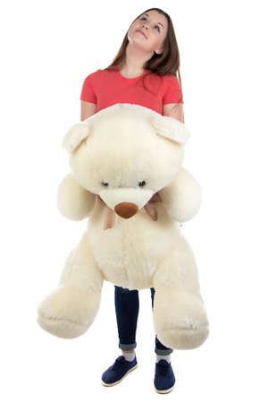 blessedness: Teenage girl looking up with teddy bear in hands on white background