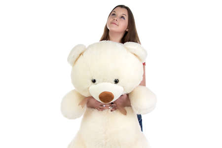blessedness: Dreaming girl looking up with teddy bear in hands on white background Stock Photo