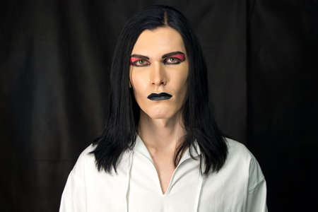 Portrait of man with make up on black background photo