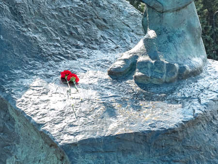 Image of gray monument with two red flowers