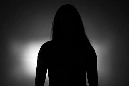 Silhouette of young  girl with long hair on dark background Standard-Bild