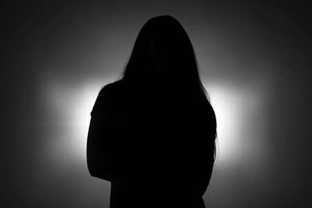 Silhouette of standing younggirl with long hair on dark background