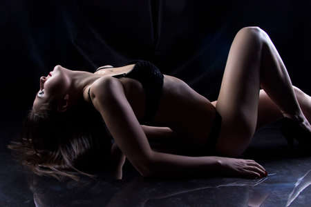 hot breast: Photo of young woman lying on the floor on black background Фото со стока