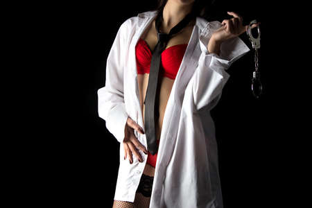 Photo of woman in mens shirt with pair of handcuffs on black background
